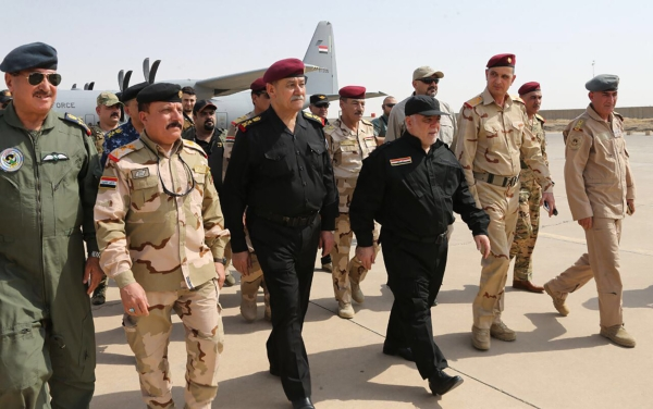 """A handout picture released by the Iraqi prime minister's press office on Sunday shows Iraqi Prime Minister Haider Al-Abadi (3rd from R) walking alongside police and army officers upon his arrival in Mosul. Abadi declared victory in the """"liberated"""" city of Mosul, his office said, after a grueling nearly nine-month battle against the Daesh group. — AFP"""