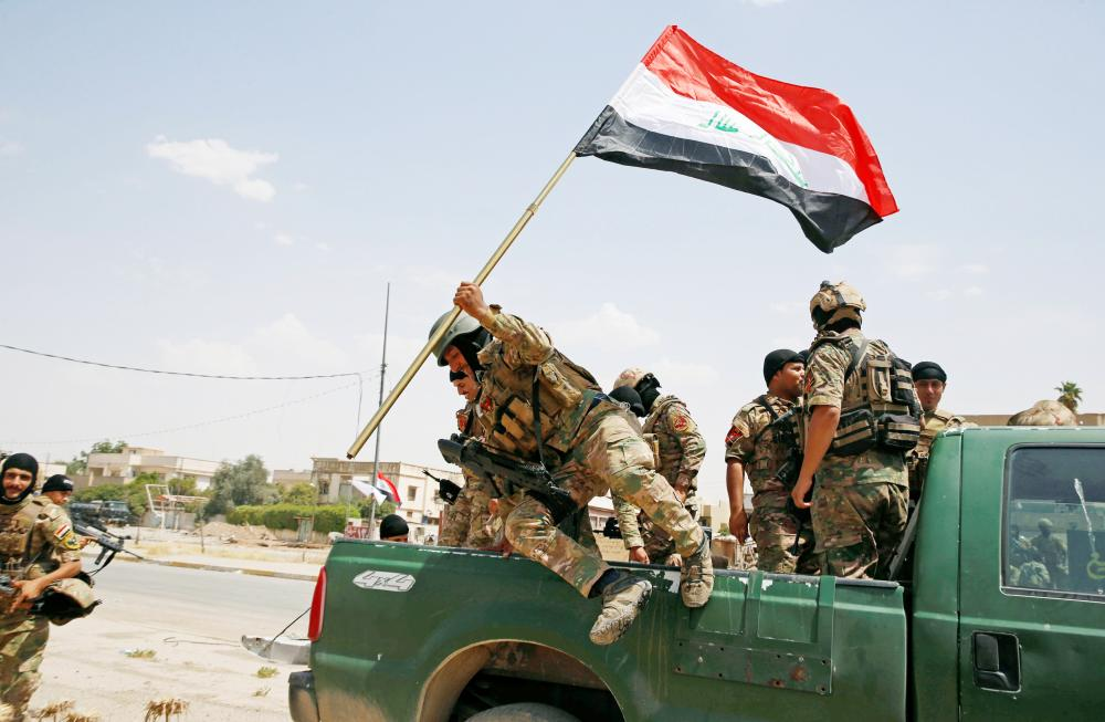 A soldier holds an Iraqi flag and jumps off a car before the start of a victory celebration after defeating Daesh militants in Mosul.