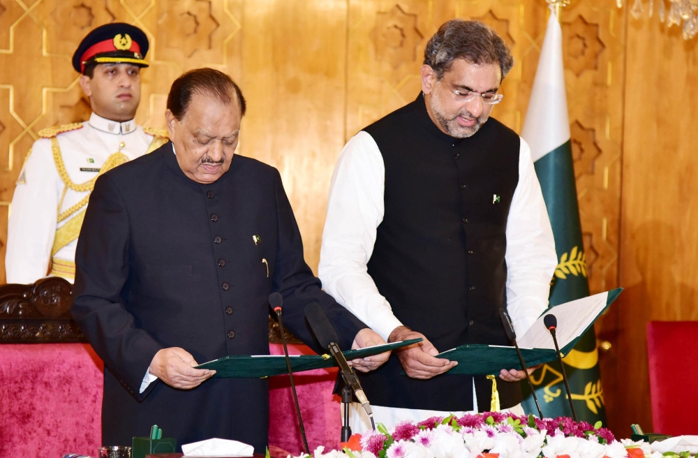 Pakistan's President Mamnoon Hussain, left, administers the oath to newly-elected Prime Minister Shahid Khaqan Abbasi during a ceremony at the Presidential Palace in Islamabad on Tuesday. — Reuters