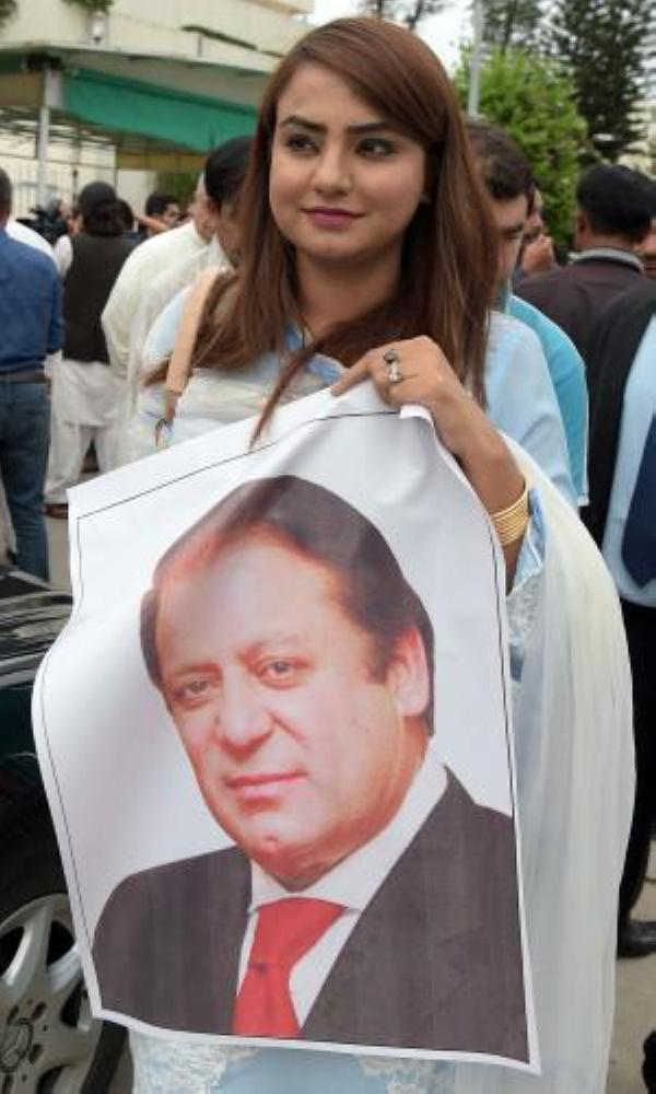 A Pakistani parliamentarian from the ruling Pakistan Muslim League-Nawaz (PML-N) party Maiza Hameed holds a poster of ousted Prime Minister Nawaz Sharif outside Parliament House after the election of a new prime minister in Islamabad in this Aug. 1, 2017 file photo. — AFP