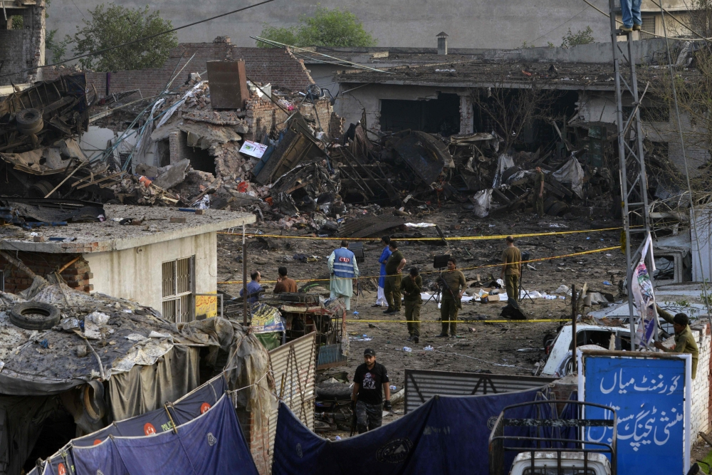Pakistani security officials investigate the site following an overnight bomb explosion placed inside a truck in Lahore on Tuesday. — AFP