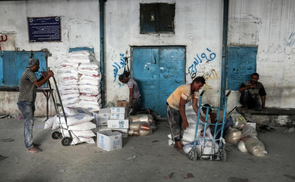 Palestinians unload sacks of food aid provided by the United Nations Relief and Works Agency for Palestine refugees (UNRWA) in the town of Rafah, in the Southern Gaza Strip. — AFP