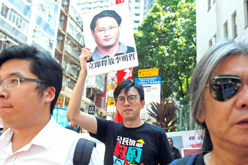 Pro-democracy protesters carry a photo of detained Taiwanese rights activist Lee Ming-Che during a demonstration in Hong Kong, China, on Monday. — Reuters