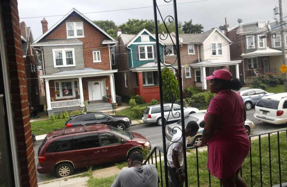 In this July 27, 2017 photo, Maria Williams stands on her front porch in Wilmington, Delaware, the day after her teenage son and daughter were shot and wounded while standing on the same porch. As she took cover inside and heard her kids' screams,