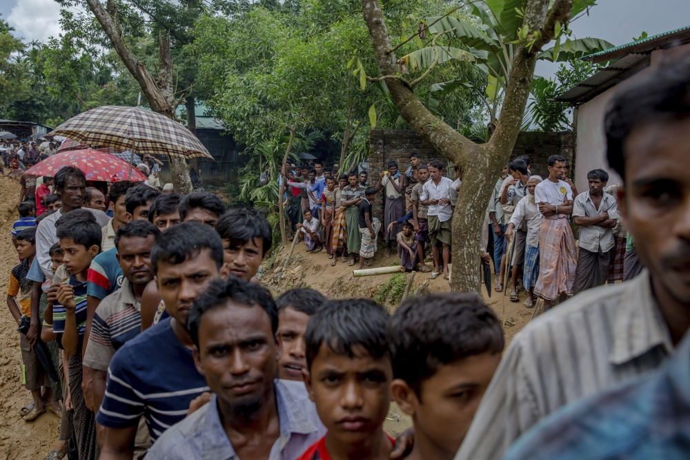 Newly arrived Rohingya wait for their turn to collect building material for their shelters distributed by aid agencies in Kutupalong refugee camp, Bangladesh, on Wednesday. — AP