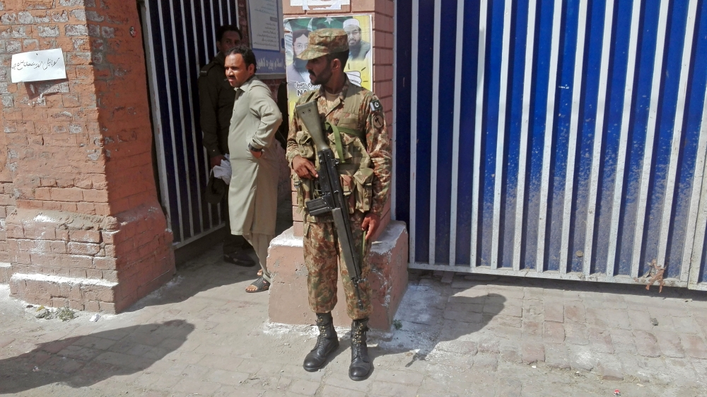 A soldier stands guard as a voter comes out of a polling station in Lahore, Pakistan, on Sunday. — Reuters
