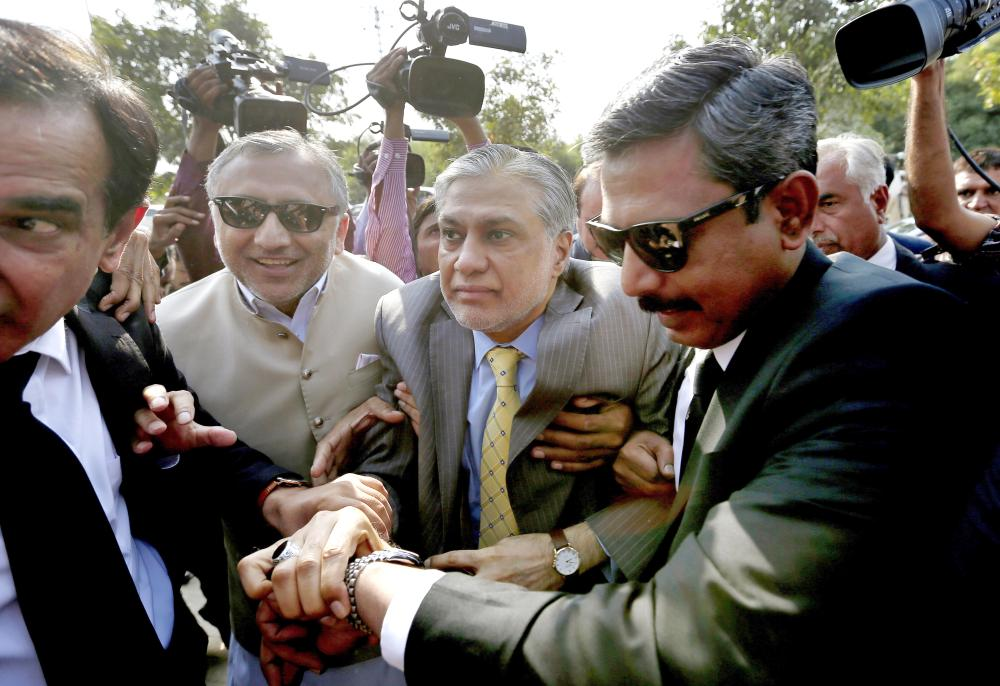 Pakistan's Finance Minister Ishaq Dar, center, arrives with his lawyer Amjad Pervez, right, to appear in an accountability court in Islamabad, Pakistan, on Wednesday. — AP