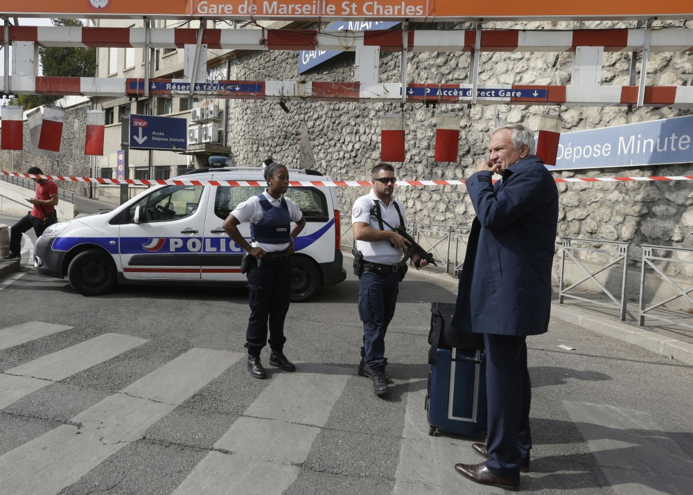 A passenger waits Marseille's main train station as French police officers patrol in Marseille, southern France, on Sunday. — AP
