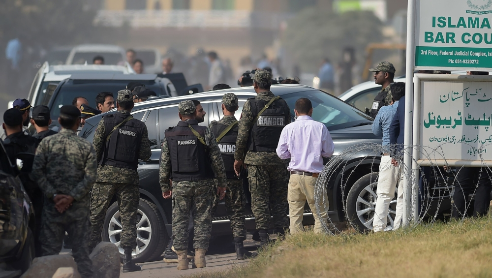 Security officials escort a vehicle carrying sacked Pakistani Prime Minister Nawaz Sharif as he arrives to appear before an accountability court to face corruption charges in Islamabad on Monday. — AFP