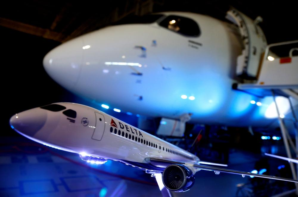 A model of a Delta airplane sits in front of the Bombardier CS100 aircraft. — Reuters