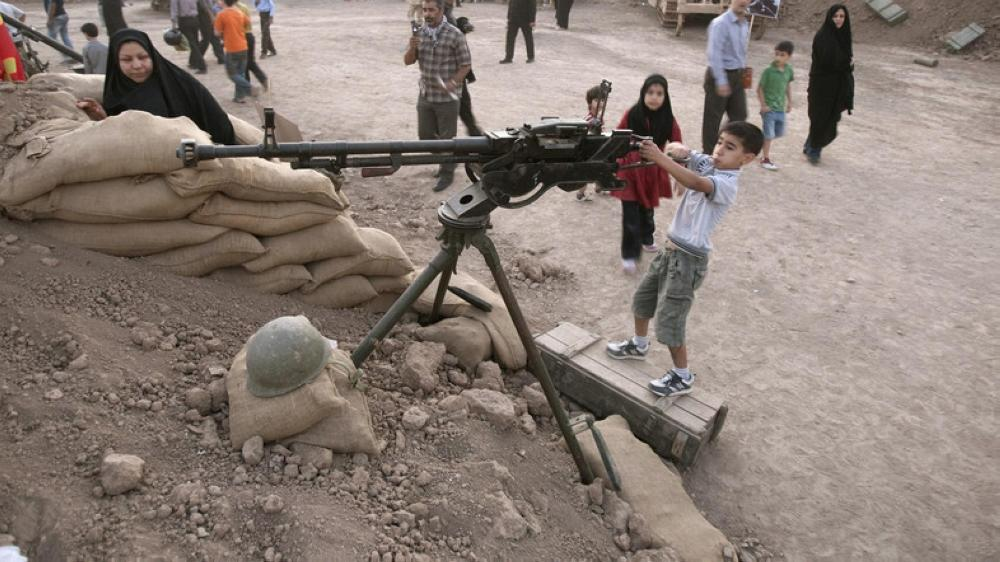 An Iranian boy plays with a weapon at a war exhibition in Tehran. — Reuters