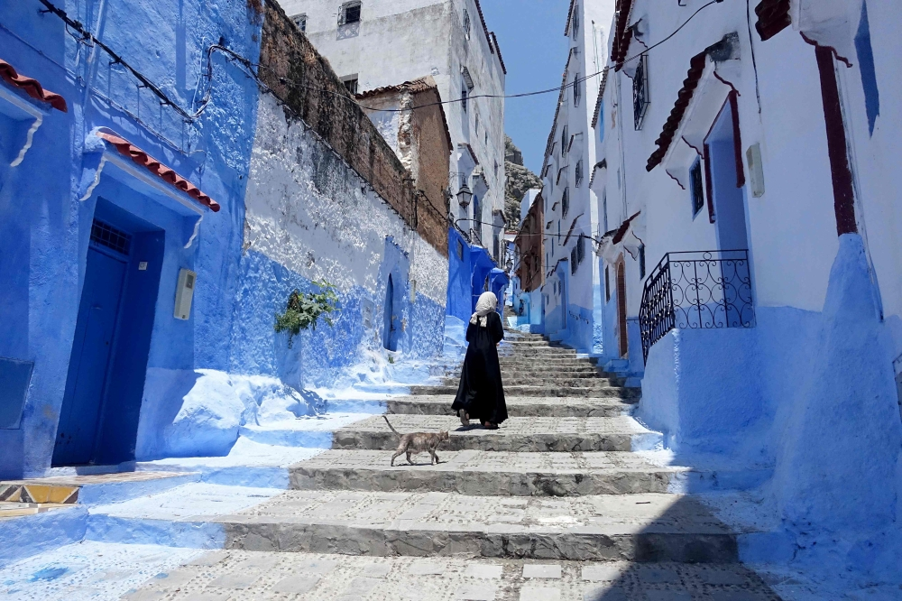 A Moroccan woman walks in Chefchaouen, in the northern Moroccan Rif region. Huddling against a hillside in northern Morocco is a tourist town famed for the striking blue of its buildings, and now the mayor is mixing in another color — green. — AFP