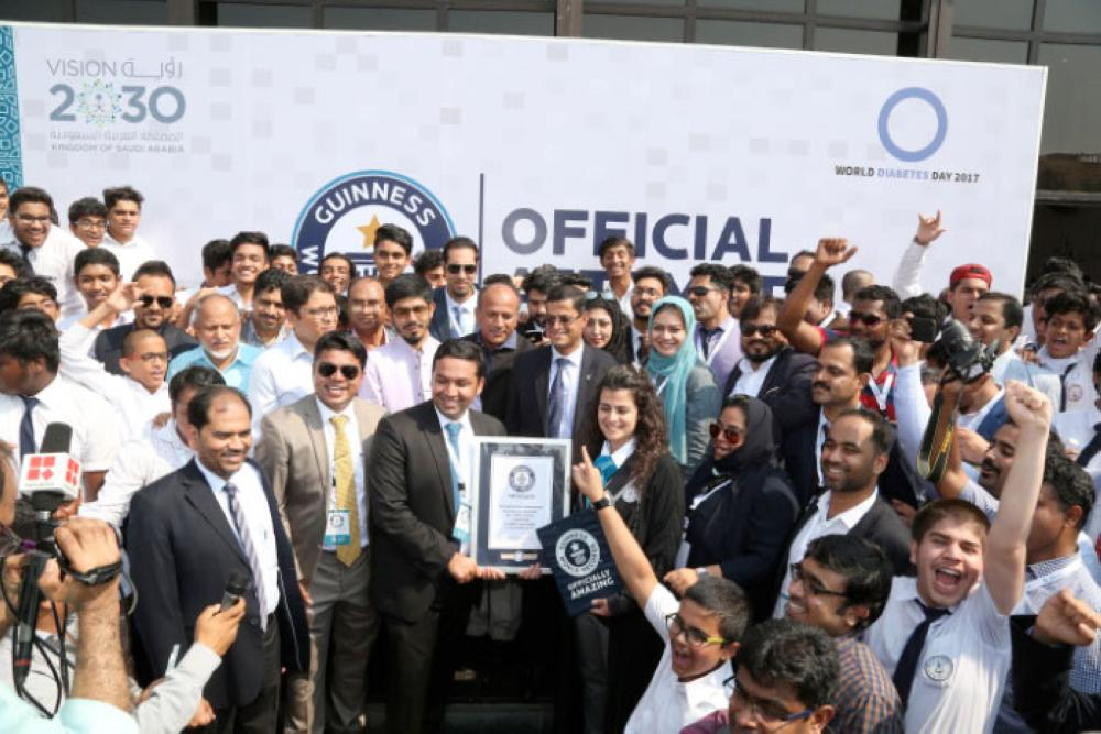 Guinness World Record's Hoda Khachab presents the recognition award after IISJ students and Abeer set the record for the largest human mosaic. — Courtesy photo