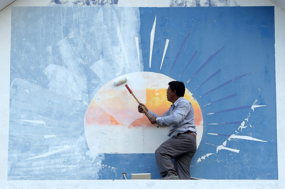 A supporter of the opposition Cambodia National Rescue Party (CNRP) paints over the party logo at the CNRP headquarters in Phnom Penh on Saturday. — AFP