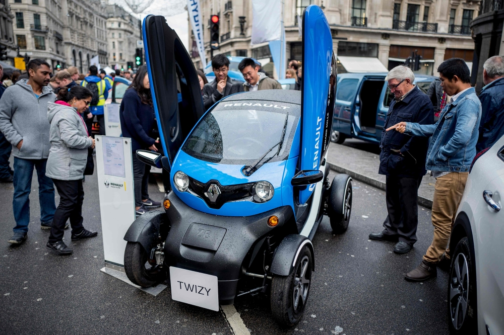 Members of public look at a Renault Twizy electric vehicle (EV) during the Regent Street Motor Show in London. A driverless, electric car is only a swipe away in the cities of the future, where pollution clampdowns and rapid advances in technology will transform the way we travel, despite lagging infrastructure. A switch from petrol to EVs is under way. Britain and France intend to ban the sale of fully petrol or diesel cars from 2040, while smog-plagued India wants to sell only electric cars by 2030. - AFP