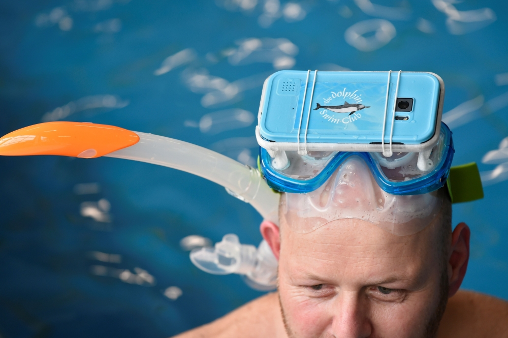 A therapist tests out new cutting-edge waterproof virtual reality glasses playing a film of dolphins, at the 'S Heeren Loo care center for disabled people in Apeldoorn, eastern Netherlands. Swimming with wild dolphins is something most can only dream of, and jumping into pools with captive animals has become increasingly controversial with environmentalists slamming it as cruel. But the Dolphin Swim Club, a Dutch non-profit, believes it has found a way to bring people, especially the disabled, closer to such a joyful experience through the technological, immersive advances offered by virtual reality (VR). - AFP