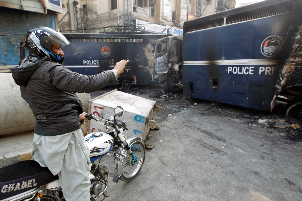 A passerby photographs police prison vans destroyed during clashes with protesters near the Faizabad junction in Islamabad, Pakistan, on Sunday. — Reuters