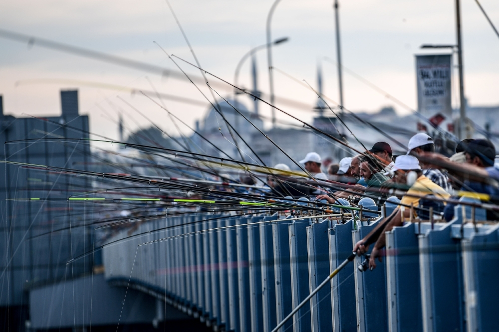 This file photo taken on Oct. 23, 2017 shows people fishing from the Galata Bridge in Karakoy district in Istanbul, as the new mosque is seen in the background. - AFP
