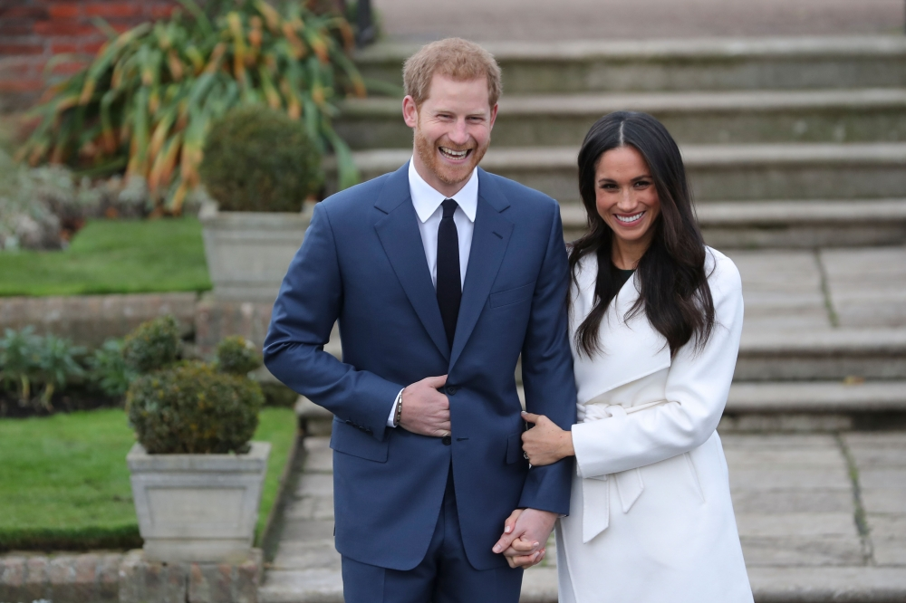 Britain's Prince Harry and his fiancée US actress Meghan Markle react as they pose for a photograph in the Sunken Garden at Kensington Palace in west London on Monday, following the announcement of their engagement. - AFP