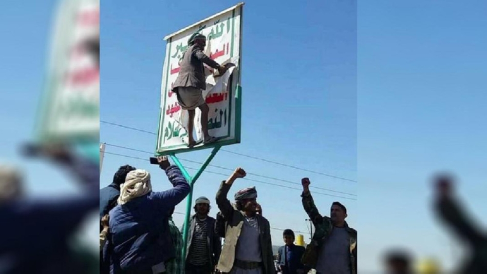 Yemenis tearing down a Houthi poster after revolting against the sectarian Iranian militia. — Courtesy Al Arabia English