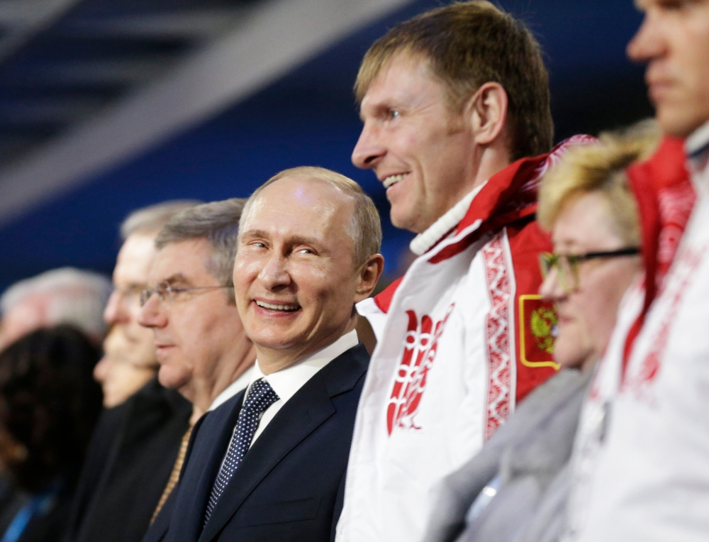 This file photo shows Russian President Vladimir Putin (C) standing next to Alexander Zubkov, gold medalist in the two-man and four-man bobsleigh for Russia, during the Closing Ceremony of the Sochi Winter Olympics at the Fisht Olympic Stadium. Russia was banned On Tuesady from the 2018 Winter Games by the International Olympic Committee (IOC) over its state-orchestrated doping program but clean Russian athletes will be allowed to compete under an Olympic flag. — AFP