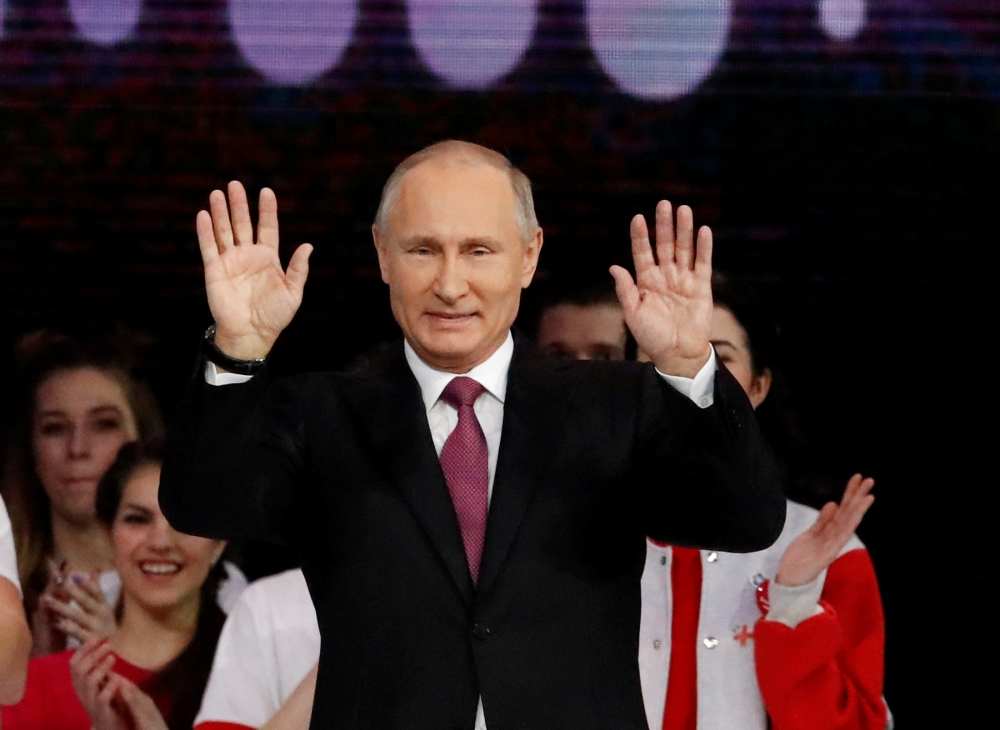 Russian President Vladimir Putin greets the audience at the congress of volunteers in Moscow, Russia, on Wednesday. — Reuters