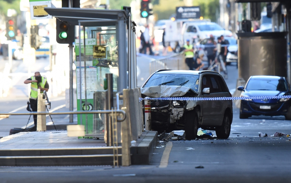 A white SUV, center, sits in the middle of the road as police and emergency personnel work at the scene of where a car ran over pedestrians in Flinders Street in Melbourne, Australia, on Thursday. — AFP