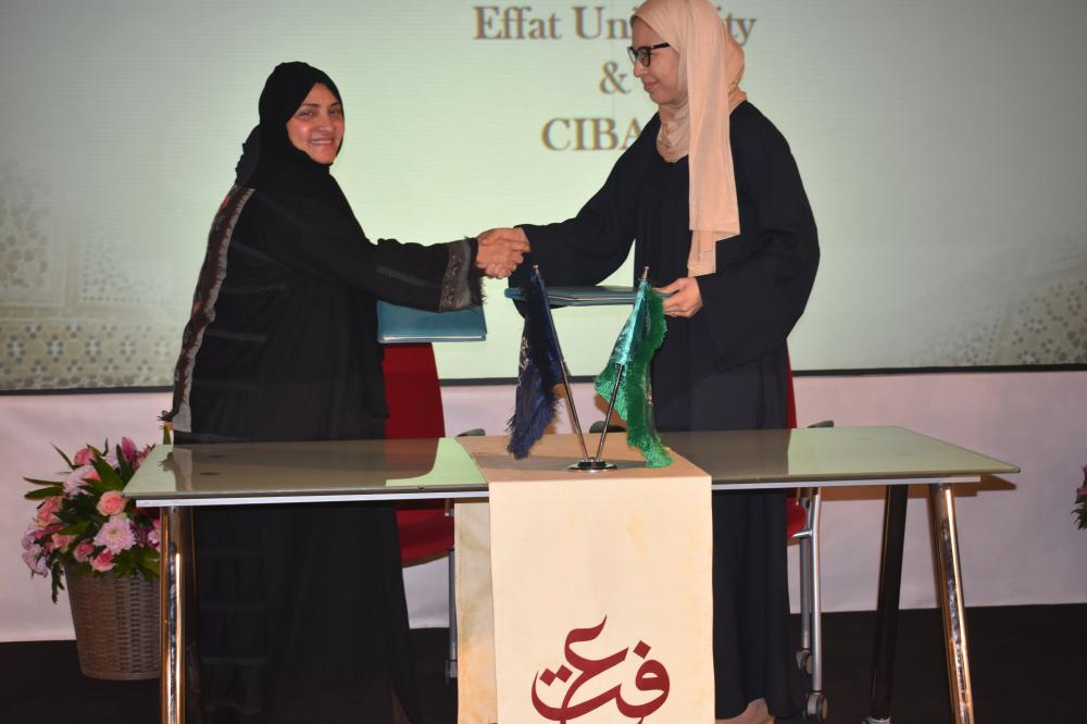 Dr. Haifa Jamal Al-Lail (L), president of Effat University, and Aziza Yarlaeva, head of strategic planning at CIBAFI, shake hands after signing the partnership agreement in Jeddah.