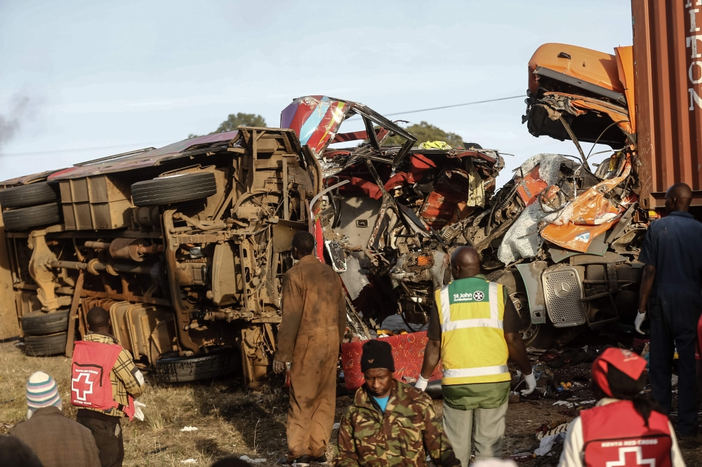 Emergency workers stand near the wreckage of a bus and a lorry that crashed in a head-on collision at the accident scene near Nakuru, Kenya, on Sunday. — AFP
