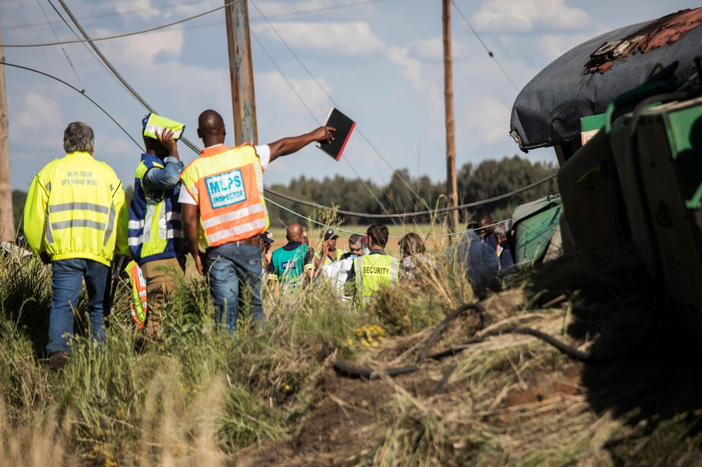 Passenger Rail Agency South Africa (PRASA) inspectors look at derailed train carriages after an accident near Kroonstad in the Free State Province, some 110 km south-west of Johannesburg, on Thursday. — AFP