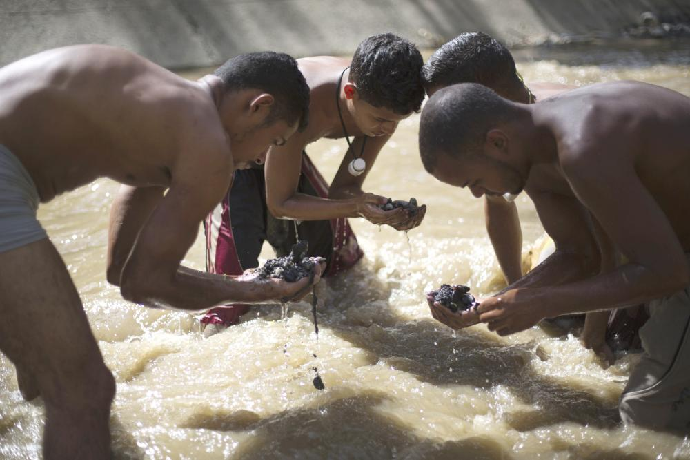 Angel Villanueva, right, looks for pieces of gold and other valuables in the debris he scooped up from the bottom of the polluted Guaire River, alongside other scavengers, in Caracas, Venezuela, in this Dec. 5, 2017 file photo. — AP