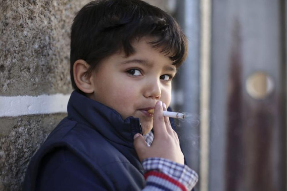 6-year-old Fernando smokes a cigarette in the village of Vale de Salgueiro, northern Portugal, during the local Kings' Feast on Sunday. - AP