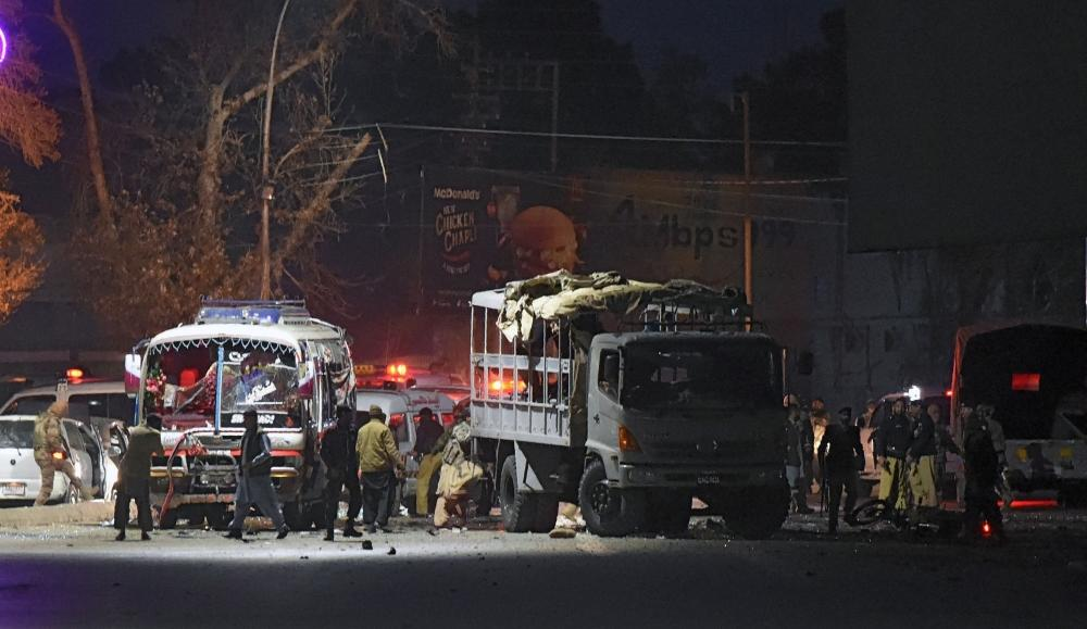 Pakistani security officials gather around a damaged police bus at the site of suicide bomb attack in Quetta Tuesday. — AFP