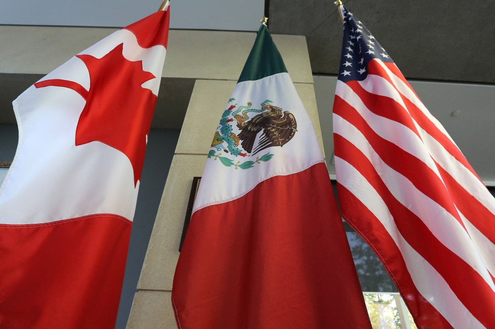 This file photo shows the Mexican, US and  Canadian flags in the lobby where the third round of the NAFTA renegotiations took place in Ottawa, Ontario. In the run-up to the latest North American Free Trade Agreement (NAFTA) renegotiations, friction is high between Canada and the US — with Ottawa determined not to bow to the Trump administration's demands, while Mexico opts for a more measured approach.Irritated by countervailing duties imposed on its exports to the US, Canada has called upon the World Trade Organization (WTO) to denounce protectionist trade practices — which it believes contradict international rules and affect other countries such as China. — AFP