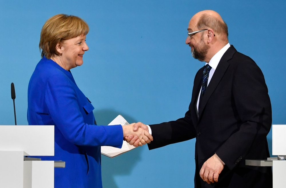 German Chancellor Angela Merkel (CDU) shakes hands with the leader of the Social Democratic Party (SPD) Martin Schulz (R) at the end of a joint press conference with the leader of the Christian Social Union (CSU), after talks to form a new government on Friday at the SPD headquarters in Berlin. — AFP