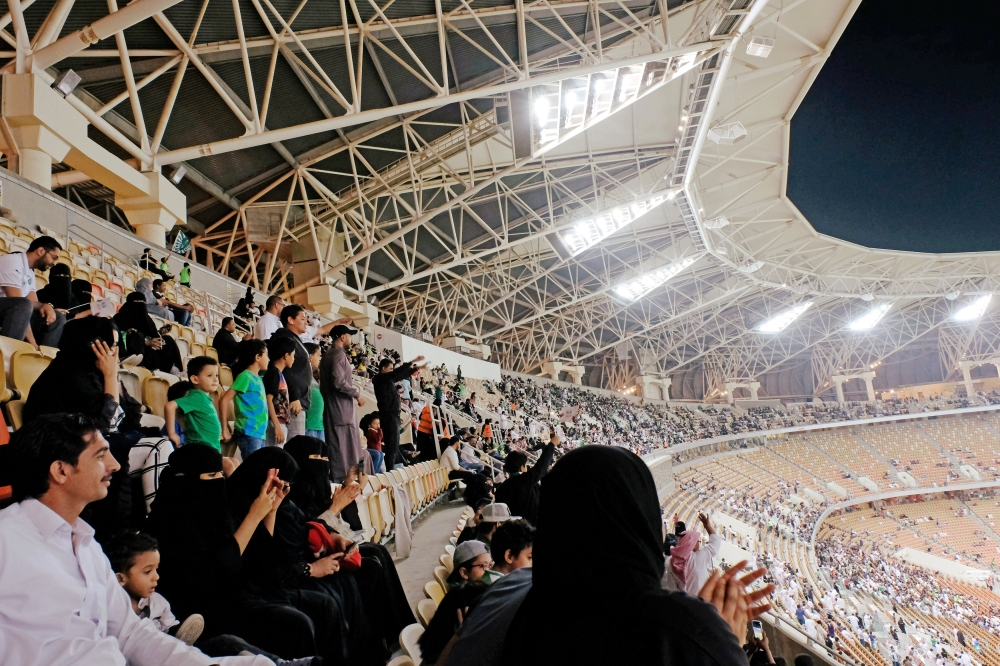 Saudi women watch the soccer match between Al-Ahli and Al-Batin at the King Abdullah Sports City in Jeddah on Friday. — Reuters