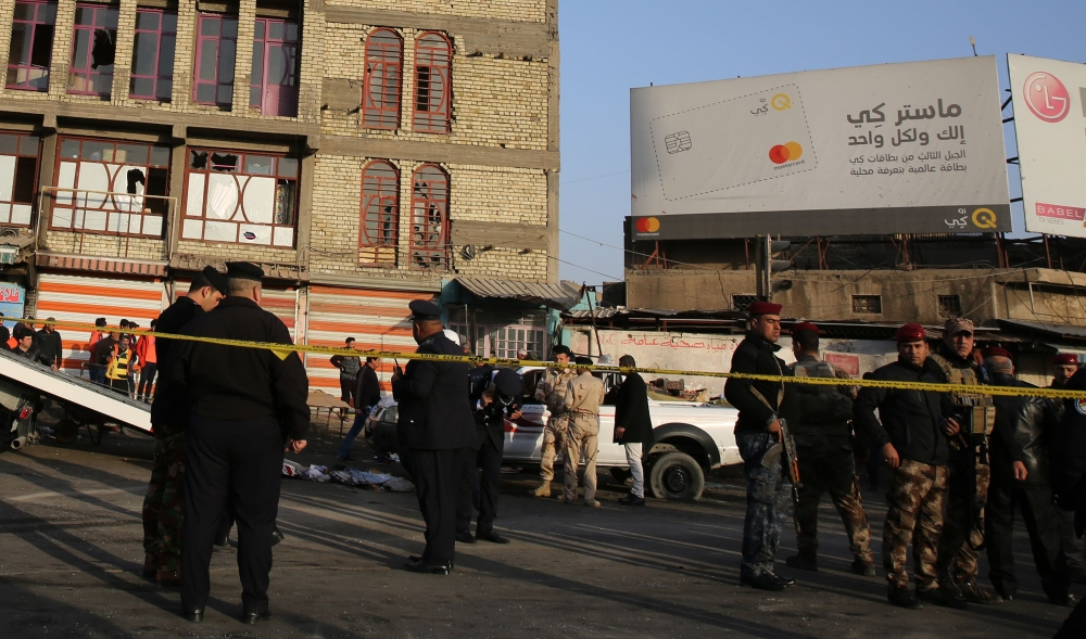 Iraqi security forces cordon off the area where a double suicide bombing killed at least 38 people in central Baghdad on Monday, the second such attack in the Iraqi capital in three days. — AFP