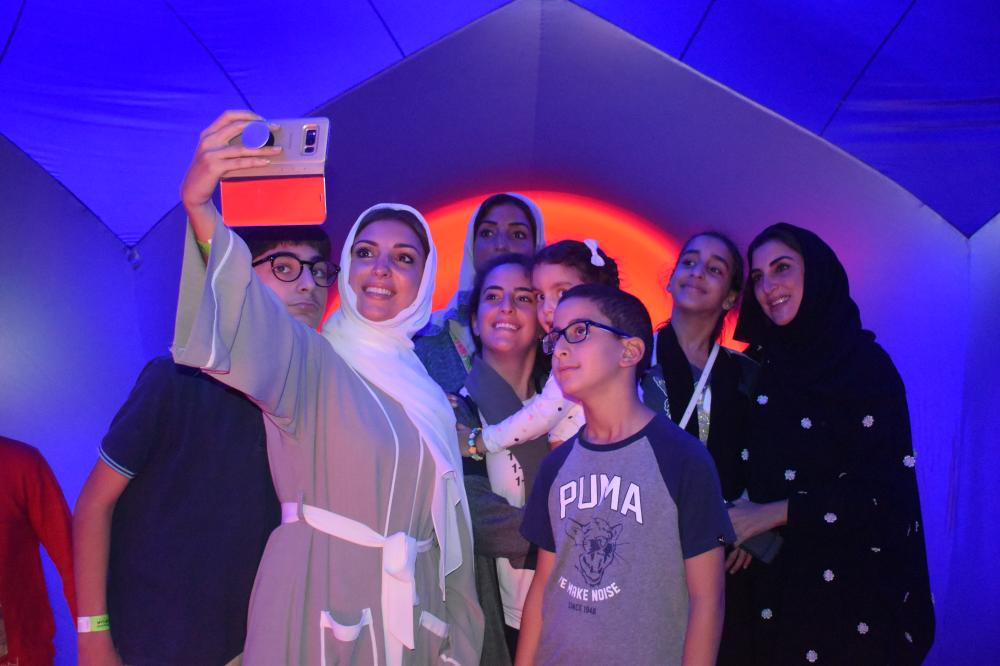A Saudi family taking a photo inside the Luminarium.
