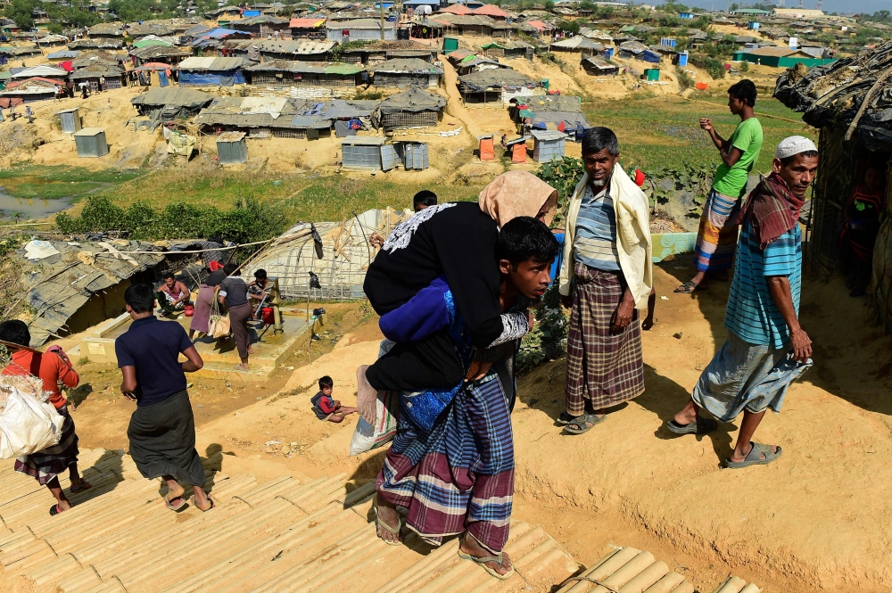 A Rohingya Muslim refugee carries his mother, who is unwell, at Kutupalong refugee camp in Bangladesh's Ukhia district, Tuesday. — AFP
