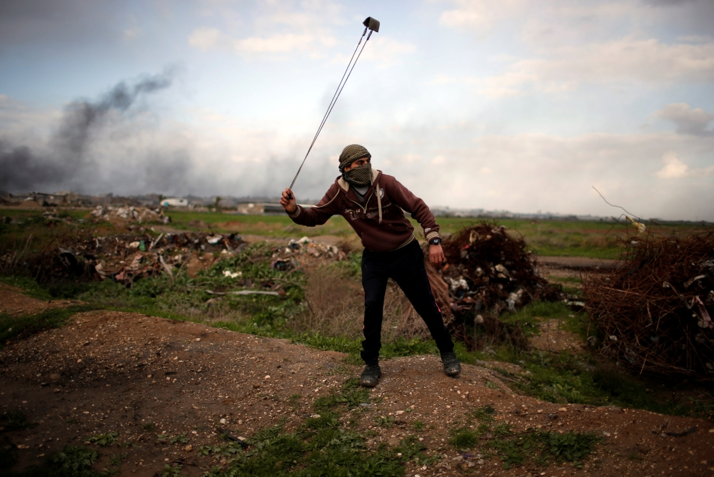 A Palestinian protester holds a sling as he poses for a photograph at the scene of clashes with Israeli troops near the border with Israel, east of Gaza City. — Reuters