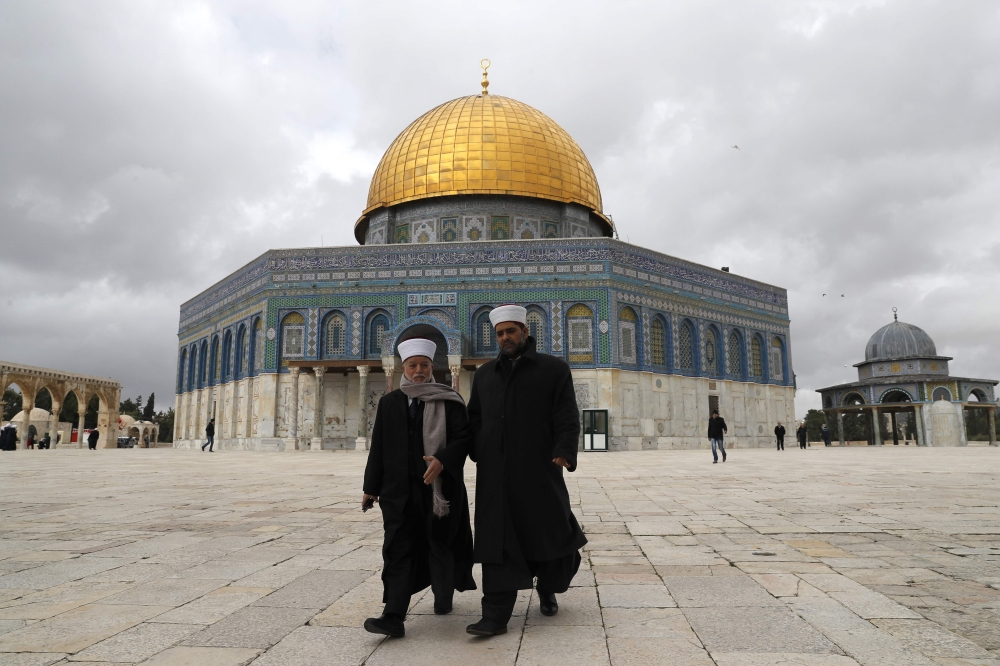 Palestinians walk outside the Dome of the Rock in Jerusalem's Old City in Al-Aqsa mosque compound. — AFP