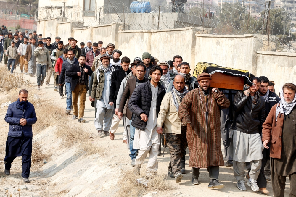 Afghan men carry the coffin of one of the victims of car bomb attack at in Kabul, Afghanistan, on Sunday. — Reuters