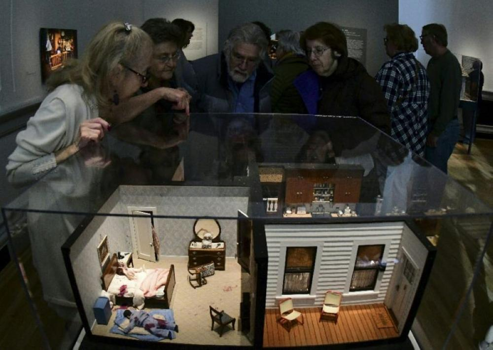 Visitors huddle around a miniature display of a crime scene featured in the exhibit