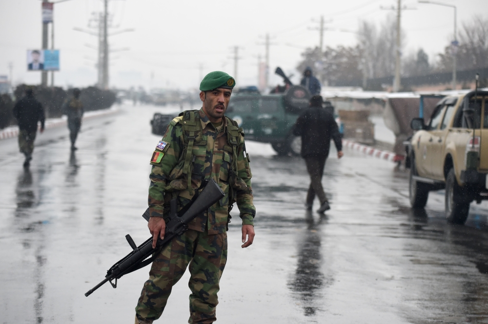 Afghan security personnel stand guard near the site of an attack near the Marshal Fahim Military Academy base in Kabul on Monday. — AFP