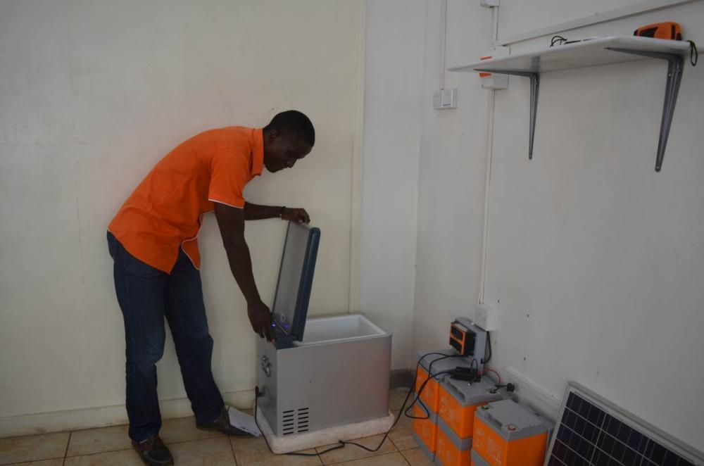 Reagan Omondi, the general manager of firm Solar Now displays a solar-powered refrigerator in Kisumu, Kenya. - Thomson Reuters Foundation