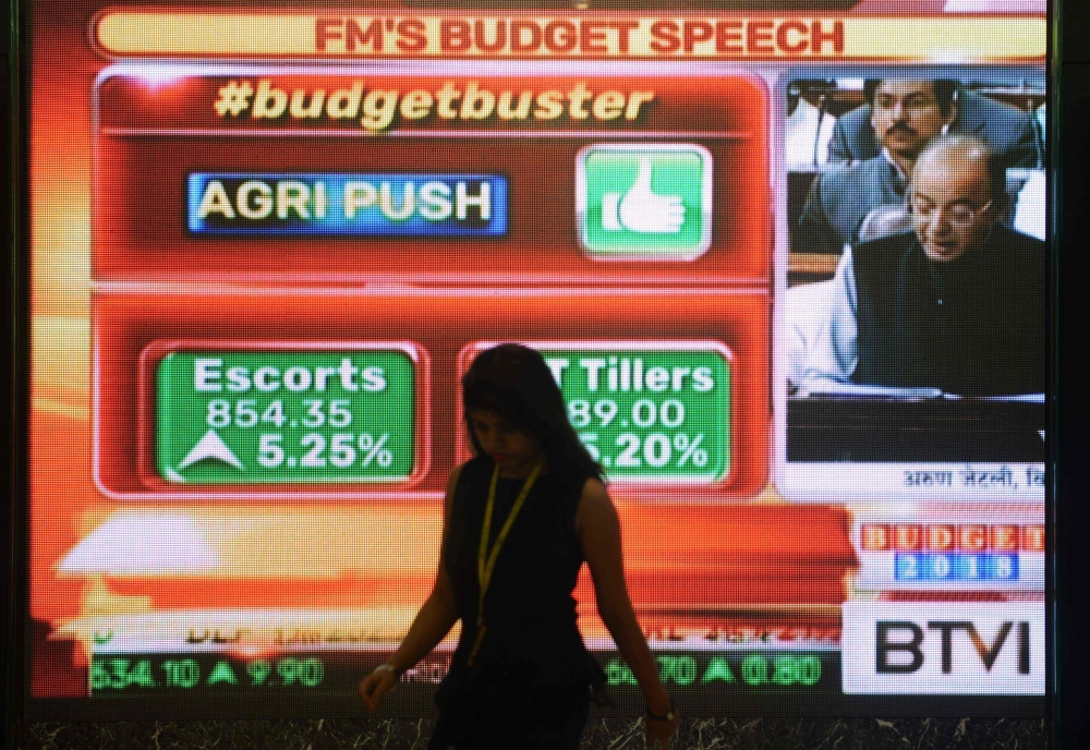 An Indian woman walks past a digital screen at the Bombay Stock Exchange (BSE) in Mumbai, showing Finance Minister Arun Jaitley delivering the budget speech at Parliament on Thursday. India promised hundreds of billions of dollars to develop poor rural areas and to help struggling farmers in its annual budget, looking to win over voters ahead of the next general election. — AFP