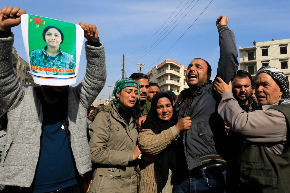A picture taken on Saturday in the town of Afrin shows the mother (3rd-L), sister (2nd-L) and brother (C) of the late 23-year-old YPJ fighter Barin Kobani, chanting slogans during a mourning ceremony in her honor, after the YPJ and the Syrian Observatory for Human Rights accused Turkish-backed Syrian rebels of filming her mutilated dead body. — AFP