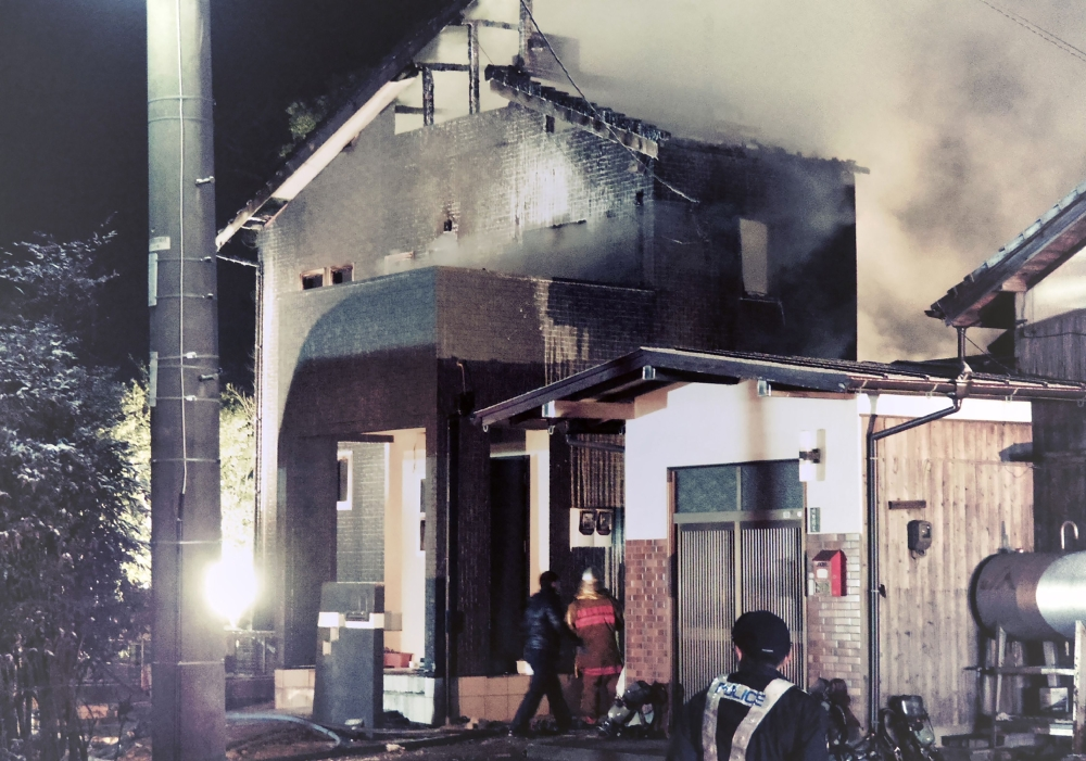 Smoke billows from a house as Japanese policemen and firefighters inspect it after a Japan's Ground Self-Defense Force's (JSFD) AH-64 Apache attack helicopter crashed in a residential area in Kanzaki, Saga prefecture, on Monday. — AFP