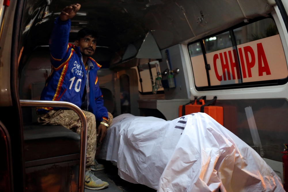 A rescue worker sits in an ambulance with a body of a Chinese man, working with a shipping company in Pakistan, who was shot dead on Monday in what police described as a targeted attack in Karachi, Pakistan, on Monday. — Reuters