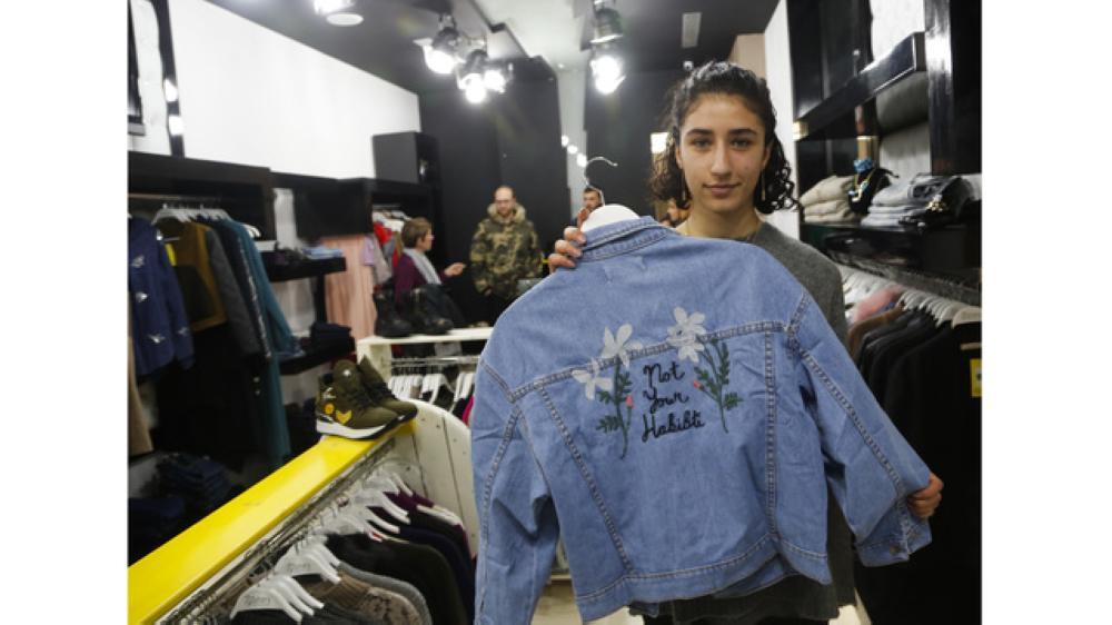 Palestinian-American Yasmeen Mjalli displays a jacket with the slogan